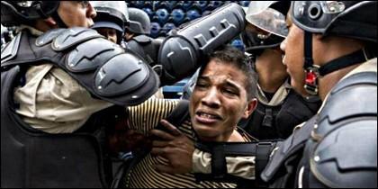 Policías chavistas reprimen a un estudiante opositor en Venezuela.