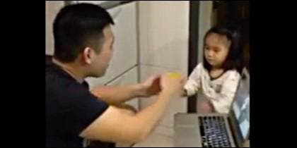 El papá, el ordenador y la niña que trae una taza de agua.