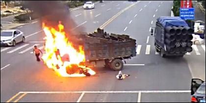 El motorista, impregnado de combustible, yace en el suelo, junto al camión en llamas.
