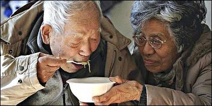 Dos ancianos japopneses se ayudan para comer.