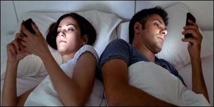 Pareja, cama, sexo y teléfono móvil.