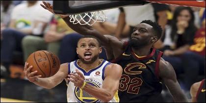 Stephen Curry encesta para los Golden State Warriors, superando a Jeff Green de los Cleveland Cavaliers, el la final de la NBA.