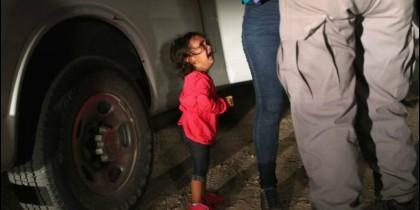 Una niña mira a un agente de la Patrulla Fronteriza de EEUU