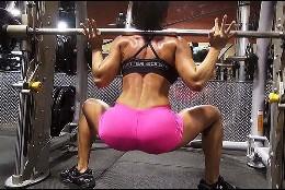 Una chica levantando pesas en el gimnasio.