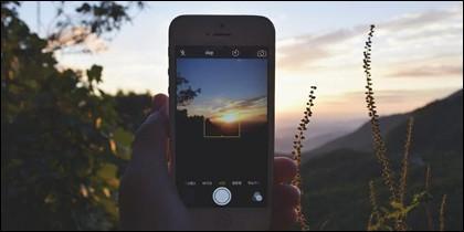 Un usuario fotografía una puesta de sol con el móvil.