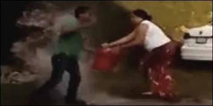 La mujer persigue a su marido con una lata de gasolina y cerillas.