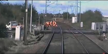 Los operarios en la via del tren en el momento en que llega el convoy