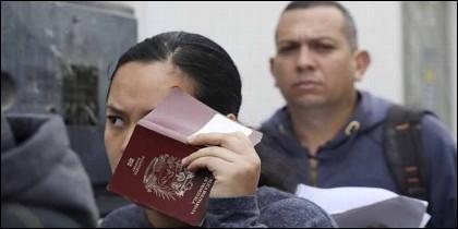 Una inmigrante venezolana tapa su rostro con un pasaporte antes de presentarse ante las autoridades de inmigración.