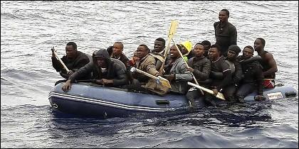 Inmigrantes subsaharianos 'sin papeles' cruzan ilegalmente de Marruecos a España, en una lancha neumática.