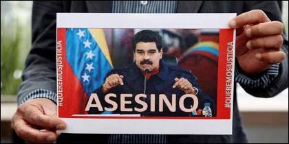 Un venezolano sostiene una fotografía del tirano Nicolás Maduro en la que se lee la palabra «Asesino».
