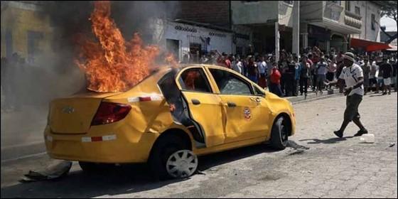 Uno de los vehículos incendiados por la turba tras el linchamientos de tres suouestos 'robaniños' en Ecuador.