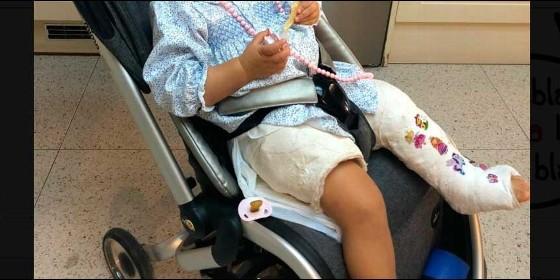 La bebé con las piernas escayoladas en su carrito de paseo