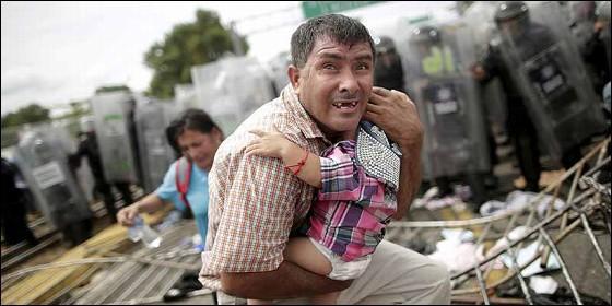 Un hondureño tarta de proteger a su hijo de la carga de la policía mexicana contra la caravana de migrantes que va hacia EEUU.