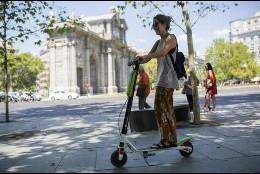 Una mujer circulando con un patinete de alquiler en Madrid
