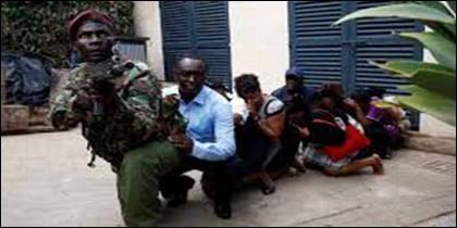 Un militar keniata trata d eproteger a clientes del hotel atacado por terroristas islámicos en Nairobi.
