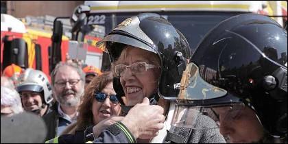 Carmena disfrazada de bombero con Barbero al fondo.