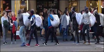 Manteros con sus bolsas, camino de la venta callejera.