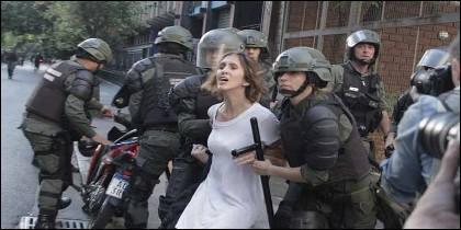 Venezuela: los esbirros chavistas arrestan a una joven en Caracas.