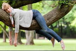 Una chica, cansada, sobre un árbol por astenia primaveral.