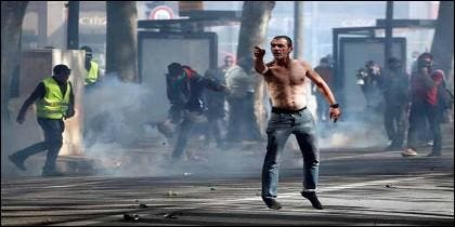 Un manifestante de los 'chalecos amarillos' reta a la policía antidisturbios en Francia.