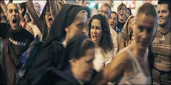 Manifestantes de Podemos hostigando a dos monjas.