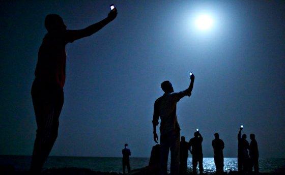 John Stanmayer gana el World Press Photo con una imagen de inmigrantes buscando 'señal'