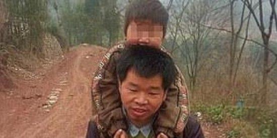 Un padre carga a su hijo paralítico a sus espaldas 28 kilómetros todos los días para que pueda ir al colegio