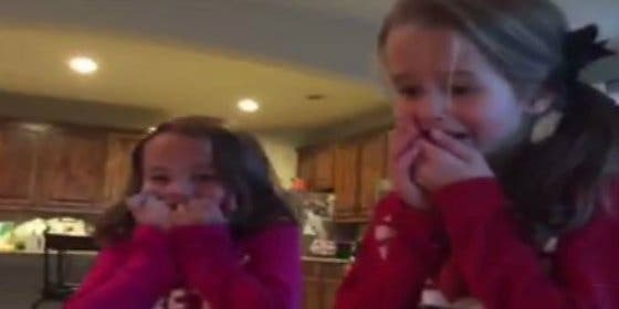 La reacción de estas niñas al ver a su nuevo hermano bajo el árbol de Navidad