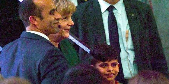 """El momento en que un """"agradecido"""" niño afgano le quiere coger la mano a Angela Merkel"""