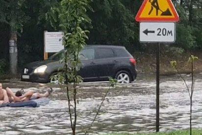 Estos rusos se divierten en calles inundadas por la lluvia con un colchón como balsa