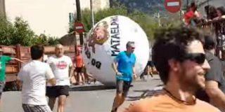 La inmensa pelota del 'boloencierro' de Mataelpino coge de gravedad a un joven