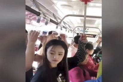 Esta chica usa un desatascador para no caer en un autobús lleno de gente