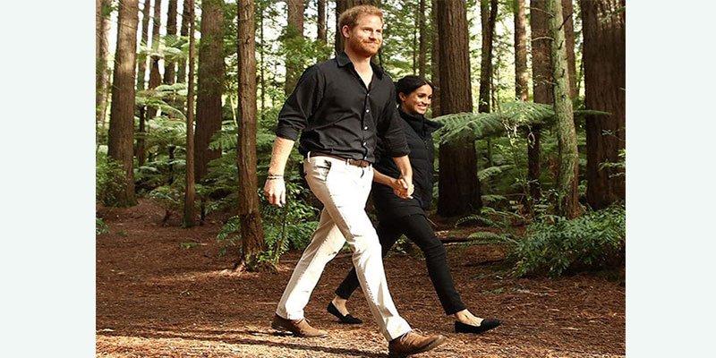 Meghan Markle y el príncipe Harry caminan de la mano por el bosque (rojo)