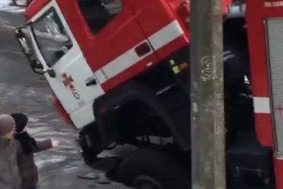 Un agujero en medio del asfalto se traga a este camión de bomberos camino de un incendio