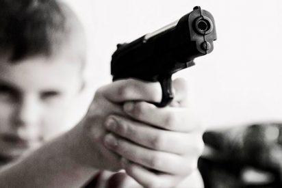 Un niño de 6 años se pasea en el patio del colegio con una pistola