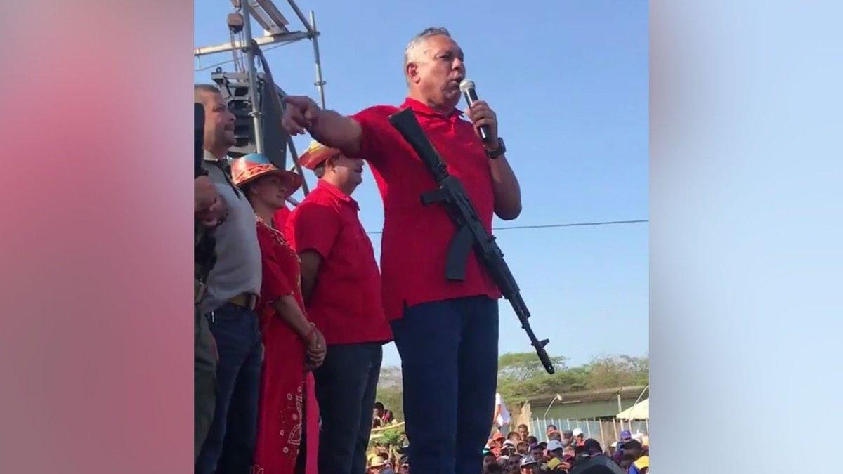 Un diputado chavista da un discurso con un fusil colgado en el cuello