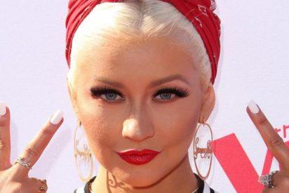 Una Christina Aguilera sin camiseta muestra su par de rifles de asalto