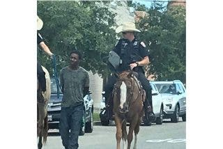 La foto de dos policías a caballo en Texas llevando a un hombre negro esposado y con una cuerda