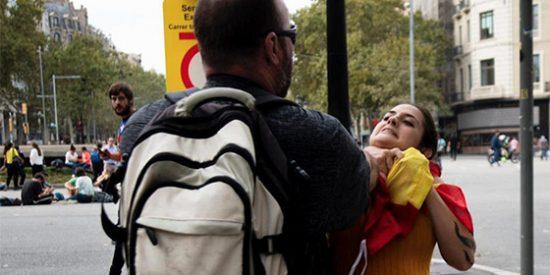 La foto que resume el violento 'tsunami independentista' del 14-O: un miserable coge por el cuello a una joven por llevar la bandera de España