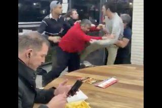 Un hombre cena impasible durante una pelea grupal dentro de un Kebab