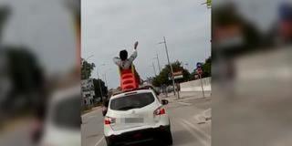 Un joven pasea por Cádiz subido a su tobogán de plástico atado a un coche