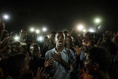 World Press Photo 2020: la impactante imagen de una protesta de jóvenes sudaneses iluminados con móviles