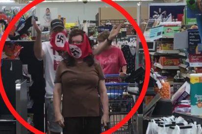 Una pareja compra en un supermercado con sus mascarillas decoradas con la esvástica nazi
