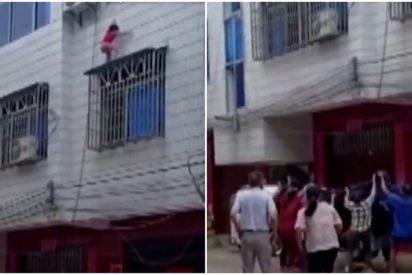 El momento en el que una niña cae por la ventana de un edificio y es atrapada al vuelo por vecinos con una manta