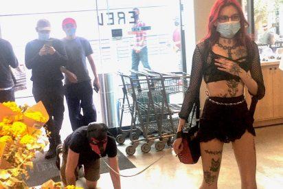 Una dominatrix tatuada pasea a un hombre atado y a cuatro patas por el supermercado