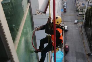 Una mujer corta la cuerda de sujeción de un trabajador suspendido en la fachada de la planta 13