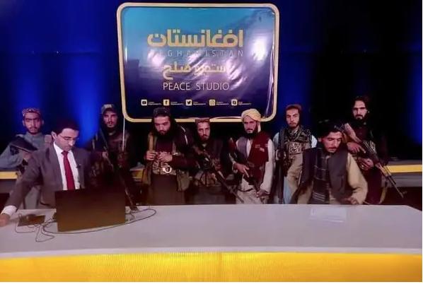 El tenso momento en que un periodista afgano transmite en TV rodeado por talibanes armados